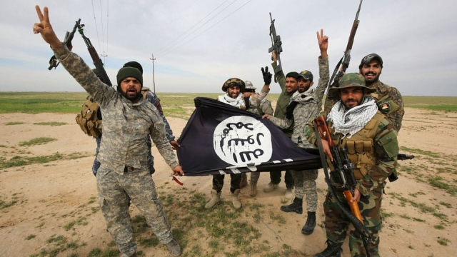 Article thumbnail: Iraqi Shiite fighters from the Popular Mobilisation units pose with an Isis flag after recapturing Samarra (Photo: Getty)