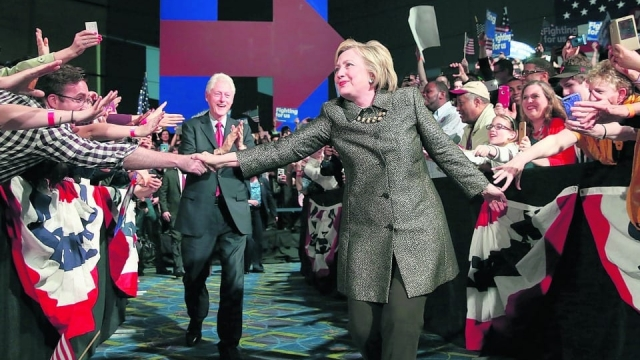 Hillary Clinton, accompanied by her husband Bill, greets supporters