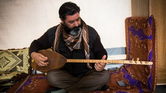 Dexil Othman performs a song in his shelter in Kaparto camp, where he lives with many other Yazidis