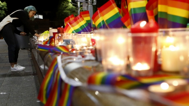 A woman lights a candle during a candlelight vigil for the victims of the Pulse Nightclub shooting in Orlando, Florida, (Photo: Daniel Munoz/Getty Images)
