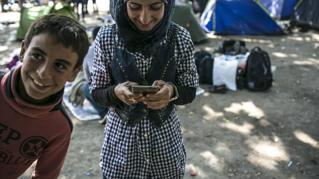 A refugee checks her smartphone on the (now-closed) Balkan route through Europe (Photo: Angel Garcia)