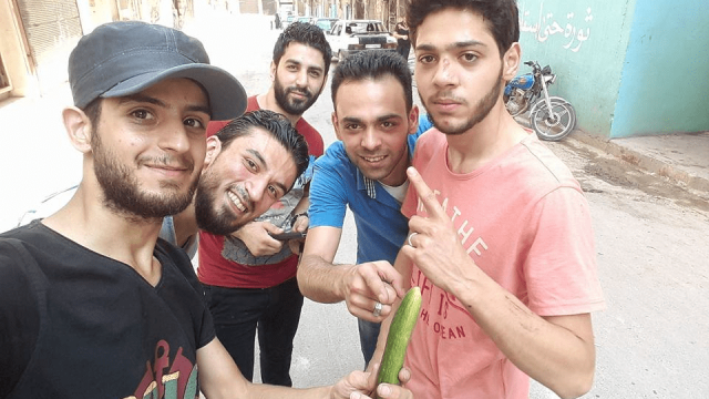 Journalists pose with a cucumber in Aleppo