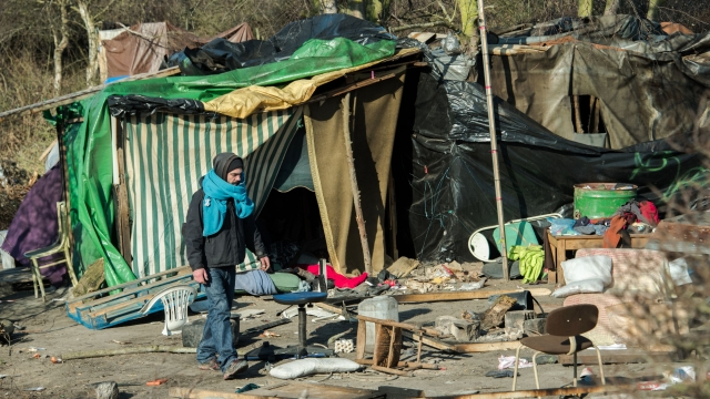 "A man walks among pieces of taken down shelters after the dismantling of the southern part of the so-called ""Jungle"" migrant camp"