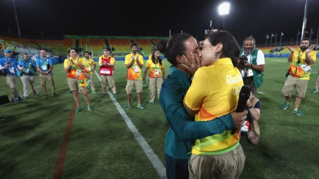 Rugby player Isadora Cerullo kisses Marjorie Enya, a volunteer, after receiving her wedding proposal on the sidelines of the women's rugby medal ceremony (Photo: Getty Images)
