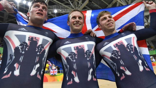 Britain's Callum Skinner, Britain's Jason Kenny and Britain's Philip Hindes hold up a British flag as they celebrate after winning gold in the men's Team Sprint track cycling finals