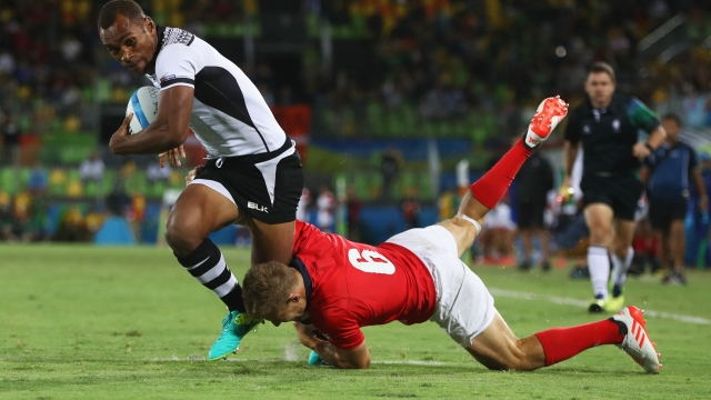 Osea Kolinisau of Fiji holds off Tom Mitchell of Great Britain to score a try during the Men's Rugby Sevens Gold medal final match