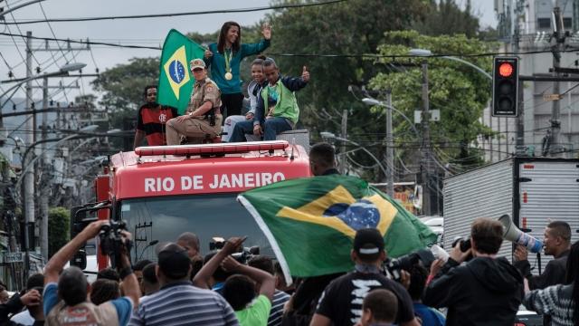 Brazilian judoka Rafaela Silva waves as she parades with her gold medal at Cidade de Deus favela, where she was born, after the Rio 2016 Olymmpic Games