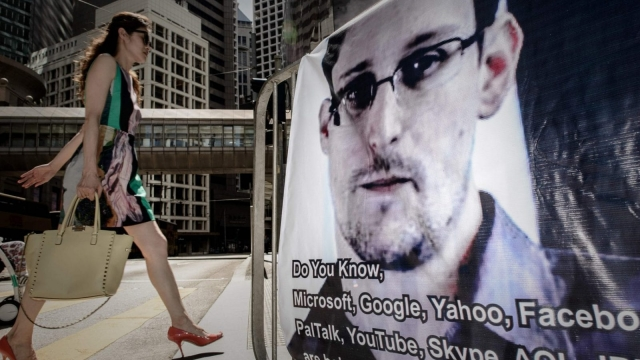 A woman walks past a banner displayed in support of US intelligence whistleblower Edward Snowden in Hong Kong. US intelligence whistleblower Edward Snowden in 2013 (Photo: AFP Philippe Lopez/Getty Images)