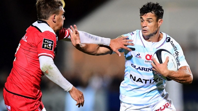 Racing 92 fly-half Dan Carter (right) fends off Toulouse's Toby Flood