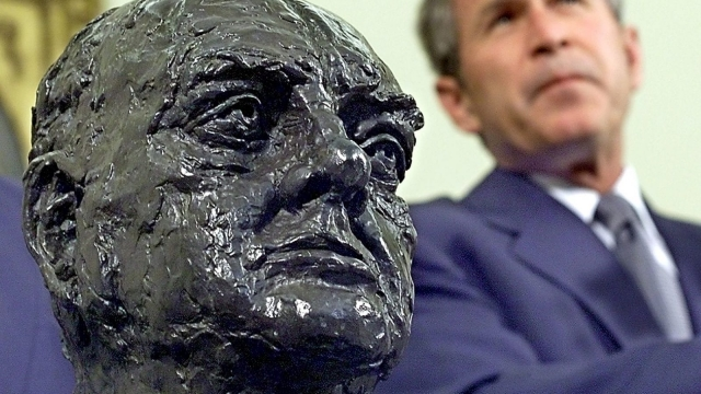 US President George W. Bush listens to journalists' questions after receiving a bust of Sir. Winston Churchill from the British Ambassador in 2001.