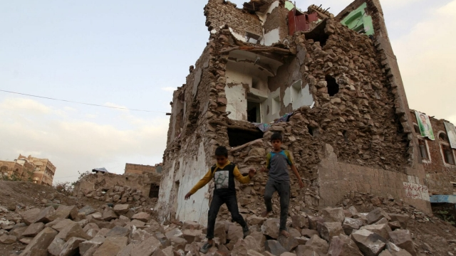 Yemeni children walk on the rubble of buildings destroyed by air strikes