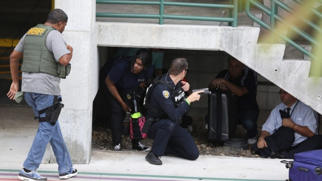 First responders assist people seeking cover outside of Fort Lauderdale-Hollywood International airport after the shooting took