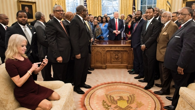 Kellyanne Conway checks her phone after taking a photo as US President Donald Trump and leaders of historically black universities and colleges pose in the Oval Office (Photo: Getty)
