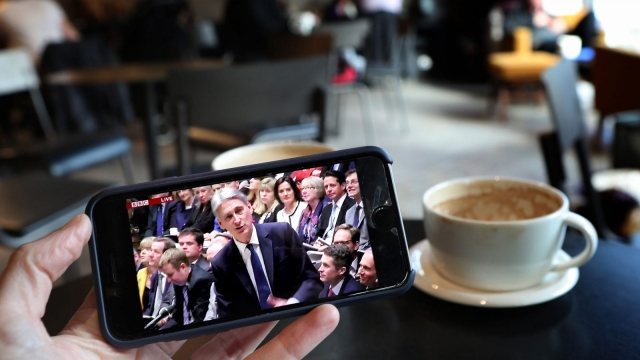A customer at a cafe in Edinburgh watches Philip Hammond deliver his Budget (Photo: PA)
