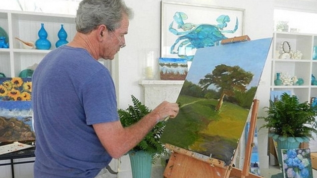 George W Bush concentrates on painting a landscape. Art has been recently found to assist patient wellbeing. (Photo: ABC News)