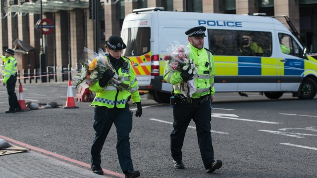 Police officers arrive with floral tributes on Westminster Bridge following Wednesday's attack in which one police officer was killed (Photo: Getty)