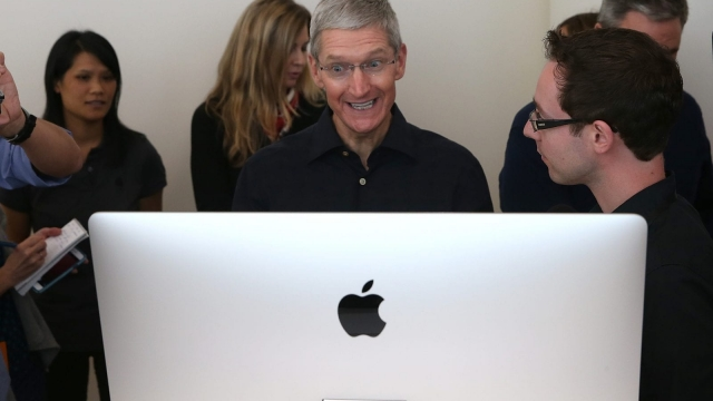CUPERTINO, CA - OCTOBER 16: Apple CEO Tim Cook looks at the new 27 inch iMac with 5K retina display during an Apple special event on October 16, 2014 in Cupertino, California. Apple unveiled the new iPad Air 2 and iPad Mini 3 tablets and the iMac with 5K retina display. (Photo by Justin Sullivan/Getty Images)
