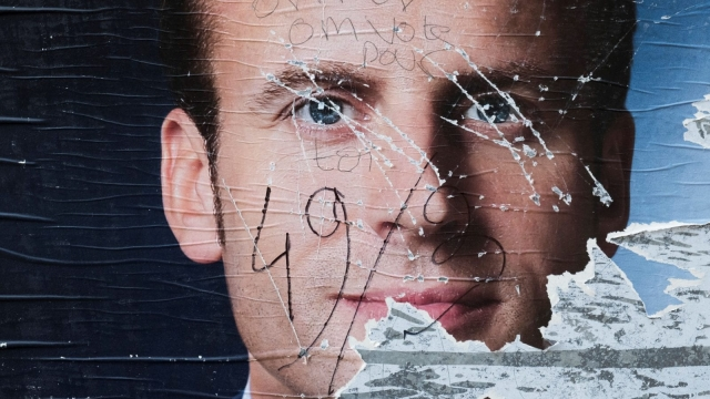 A picture taken in Paris, on May 5, 2017, shows vandalised campaign posters of French presidential election candidate for the En Marche ! movement, Emmanuel Macron (Photo: Getty)
