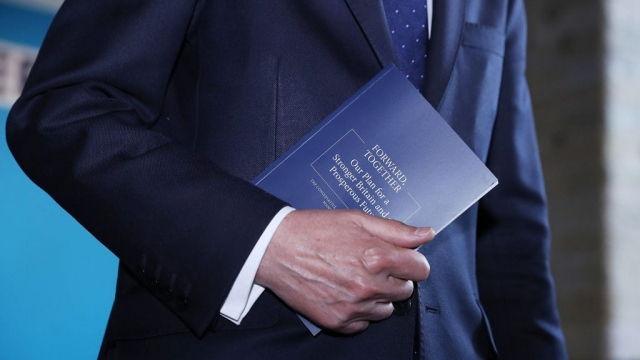 Chancellor Philip Hammond holds a copy of the Tory manifesto (Photo: Getty)