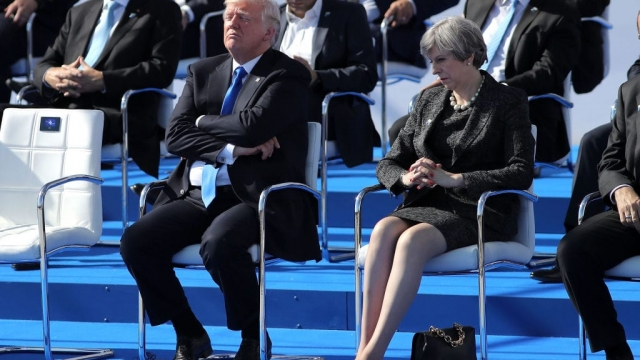 Donald Trump rests during a photo opp at the Nato summit next to Theresa May (Photo: Getty)