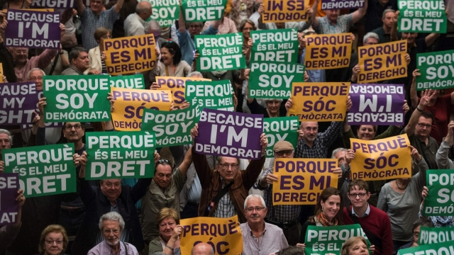 """Attendees hold posters reading """"Because I'm democrat"""" and """"Because it's my right"""" during a political rally supporting a referendum on Catalonian independence (Photo: Getty)"""
