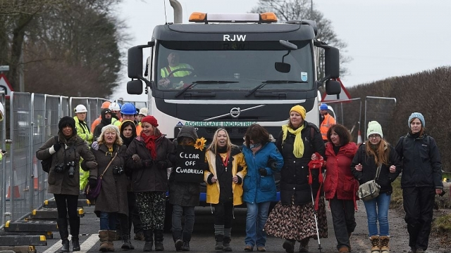 Anti-fracking protesters slow-walk in front of a gravel truck delivering at the Preston New Road site. (Photo: Paul Ellis/AFP/Getty Images)