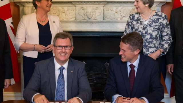 Sir Jeffrey Donaldson, front left, signs the deal with the Conservatives as DUP leader Arlene Foster, Prime Minister Theresa May and Government whip Gavin Williamson look on (Photo: Getty)