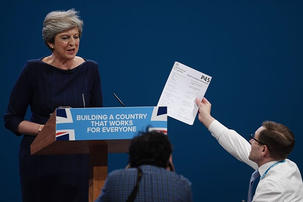 Comedian Simon Brodkin, aka prankster Lee Nelson, hands Prime Minister Theresa May a P45 during her keynote speech to delegates and party members (Photo: Carl Court/Getty)