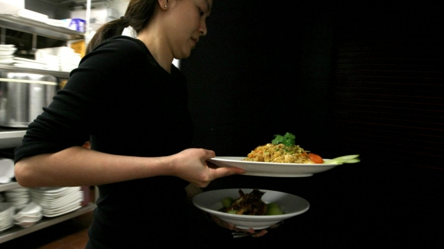 A waitress carries plates of food at a restaurant in San Francisco, US