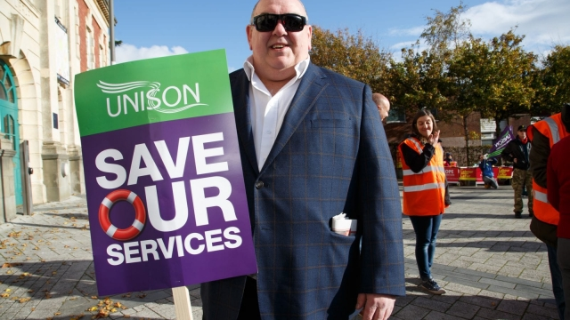 Neville Southall holds a placard for Unison at a rally in Barry, Wales