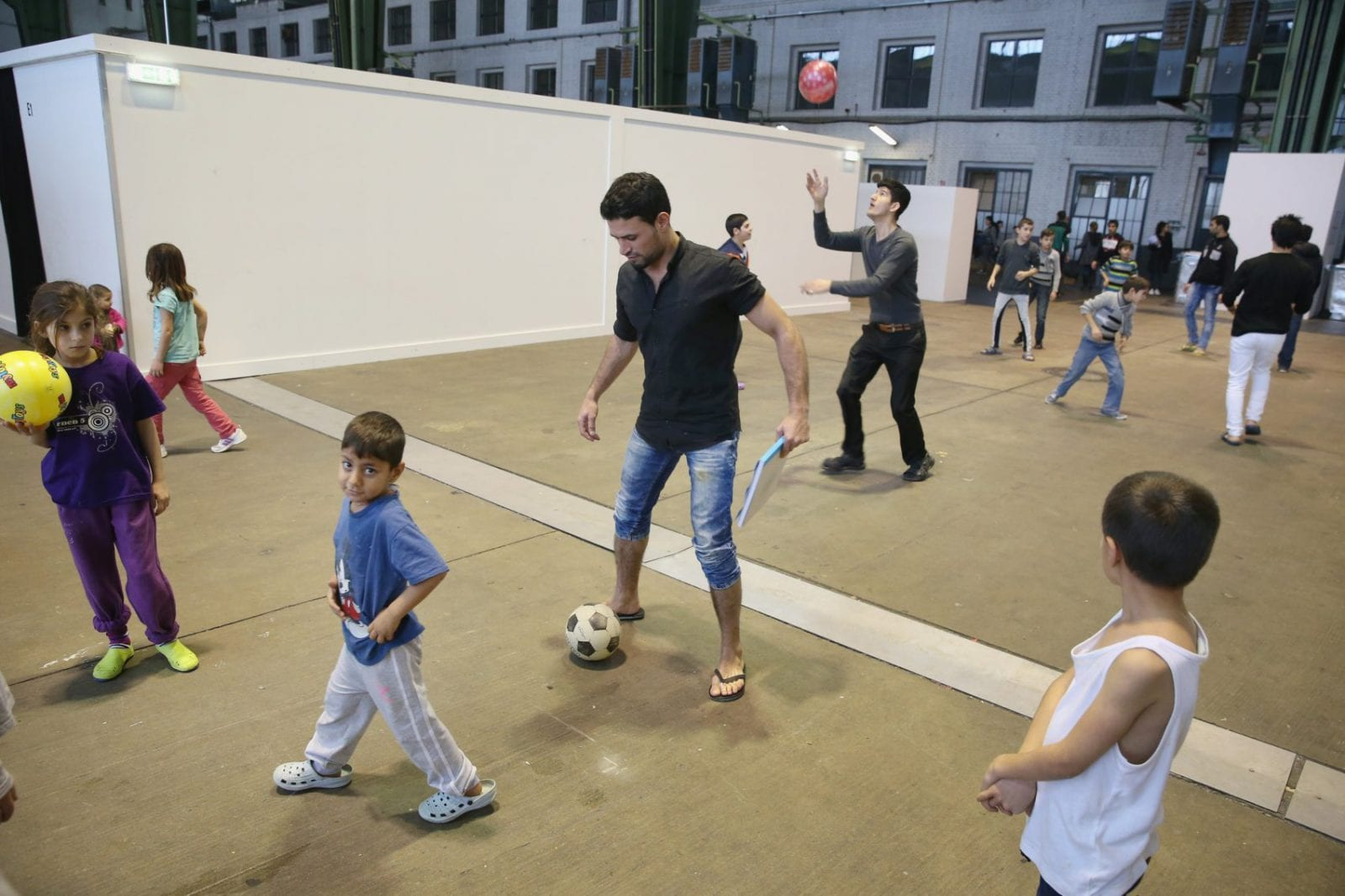 Refugees and migrants seeking asylum in Germany play with balls in Hangar 7 at former Tempelhof Airport (Photo: Getty)