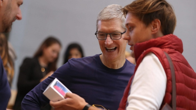 PALO ALTO, CA - NOVEMBER 03: Apple CEO Tim Cook (L) talks with a customer who just purchased the new iPhone X at an Apple Store on November 3, 2017 in Palo Alto, California. The highly anticipated iPhone X went on sale around the world today. (Photo by Justin Sullivan/Getty Images)