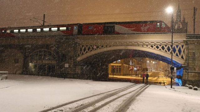 A Virgin train leaves Newcastle Train station following heavy overnight snowfall which has caused disruption across Britain (Photo: PA)