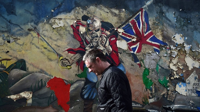A man walks past a unionist mural in Derry/Londonderry, Northern Ireland (Photo: Getty)
