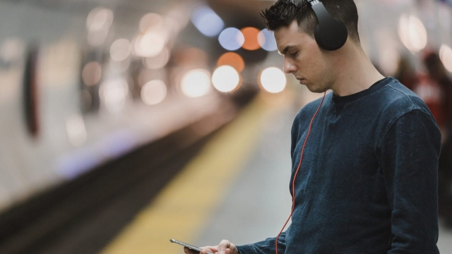 A man wearing headphones waits for a train. (Image: pexels)