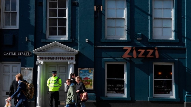 A police officer is passed by shoppers as he stands guard outside the temporarily closed Zizzi restaurant in Salisbury. (Photo: Getty)