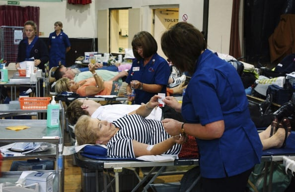 Nurses attend blood donors on beds during session at NHS National Blood Service collection centre.