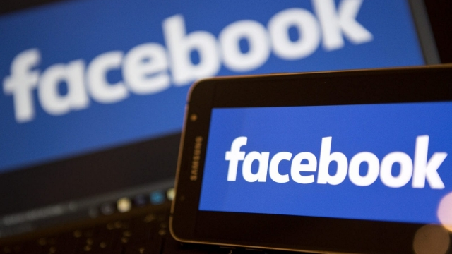 Facebook logos are pictured on the screens of a smartphone (R), and a laptop computer, in central London on November 21, 2016. Facebook on Monday became the latest US tech giant to announce new investment in Britain with hundreds of extra jobs but hinted its success depended on skilled migration after Britain leaves the European Union. The premier social network underlined London's status as a global technology hub at a British company bosses' summit where Prime Minister Theresa May sought to allay business concerns about Brexit. / AFP PHOTO / Justin TALLIS (Photo credit should read JUSTIN TALLIS/AFP/Getty Images)