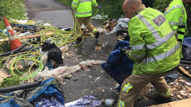 Firefighters remove dumped rubbish from the road blocking their path to an emergency. Photo: Facebook/WSF & R