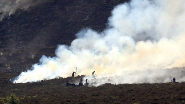 Firefighters tackle the wildfire on Saddleworth Moor. (PA)
