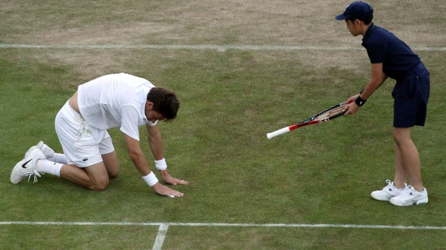 Nicolas Mahut is handed back his racket by a ballboy in the match against John Isner in 2010
