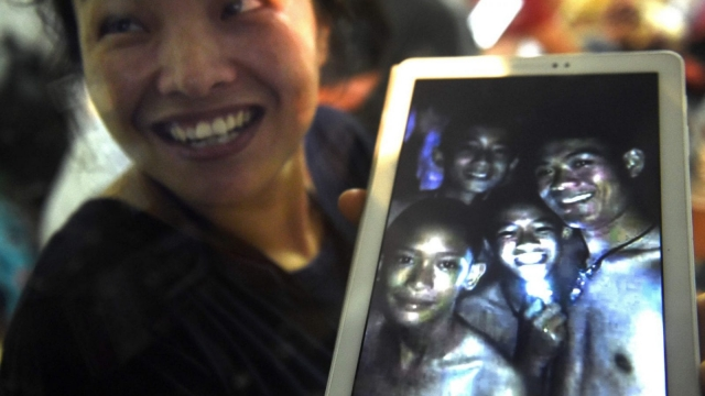 A family member shows a picture believed to have been taken in 2017 of four of the 12 missing boys after hearing the news the group was found, near the Tham Luang cave (AFP/Getty)