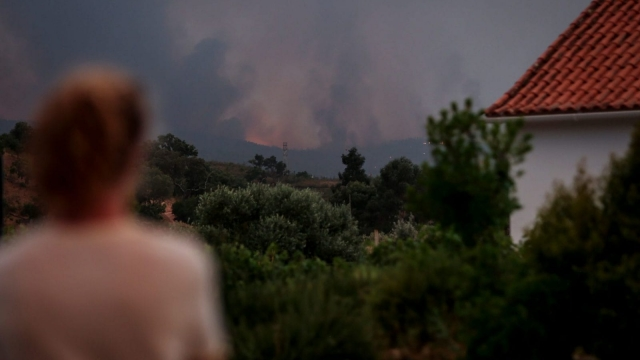 A woman watches the progression of a wildfire in the tourist zone of Monchique, Algarve in southern Portugal.