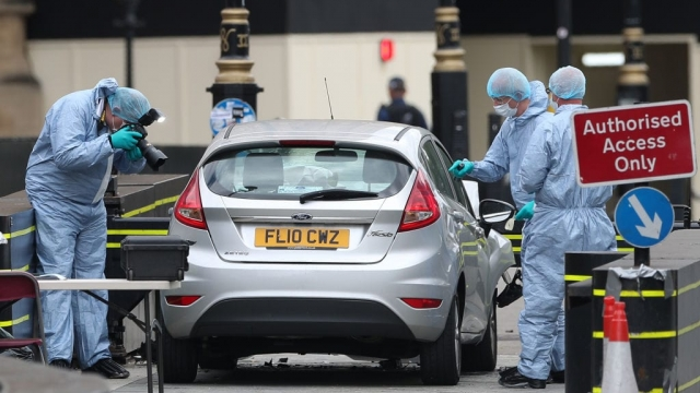 Police forensics officers work around a silver Ford Fiesta car that was driven into a barrier (Photo: Getty)