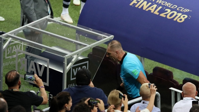 Referee Nestor Pitana reviews VAR footage before awarding France a penalty during the 2018 FIFA World Cup Final. (Getty Images)