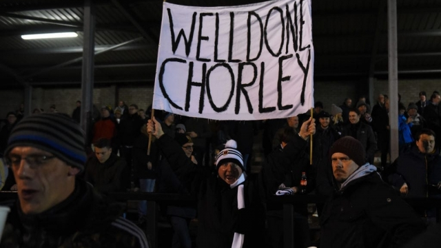 A Chorley fan holds a banner during an FA Cup match against Fleetwood Town. (Photo by Nathan Stirk/Getty Images)