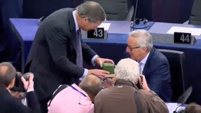 Nigel Farage gives Jean-Claude Juncker Union Jack socks.
