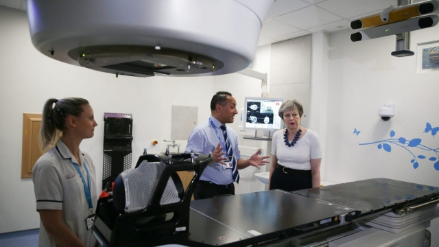 British Prime Minister Theresa May is shown the advanced radiotherapy system during a visit to announce new funding and research into prostate cancer, at Addenbrooke's Hospital in Cambridge, England in April 2018. Photo credit DANIEL LEAL OLIVAS/AFP/Getty Images.