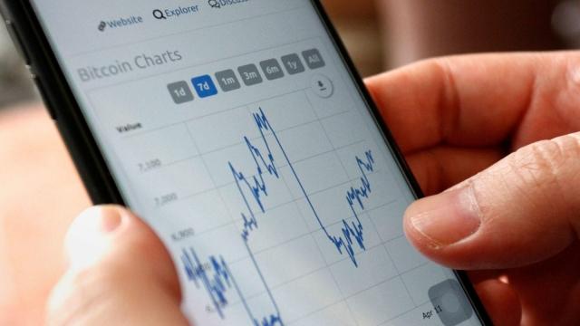 A trader checks Bitcoin prices