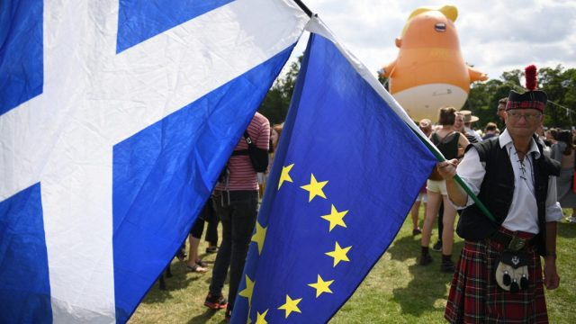 EDINBURGH, SCOTLAND - JULY 14: The Baby Trump Balloon floats in the distance as a man dressed in a kilt waves the Scottish Flag and the flag of the European Union . (Photo by Jeff J Mitchell/Getty Images)